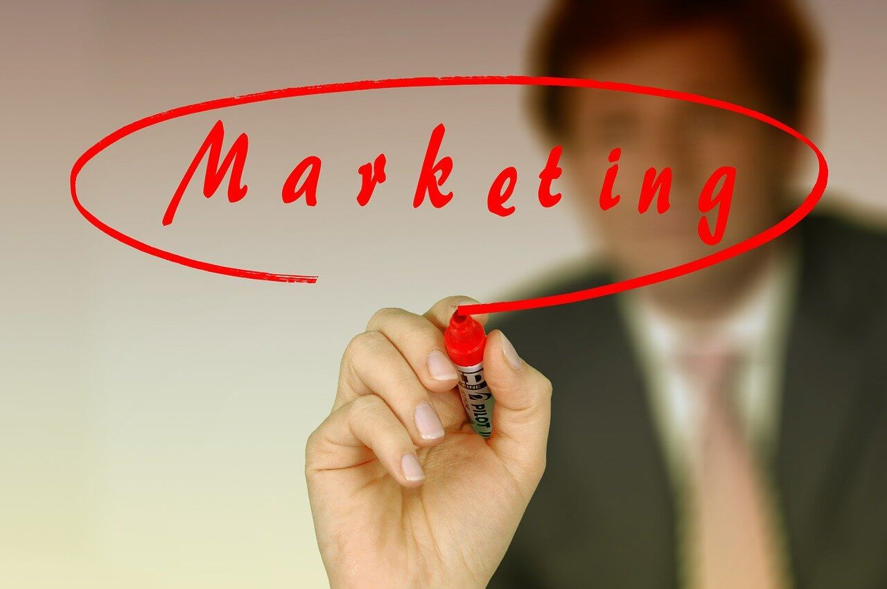 Image of a man writing the word marketing